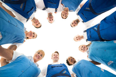 directly below: Directly below portrait of confident janitors standing in huddle against white background