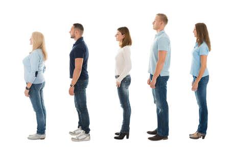 Volledige lengte zijaanzicht van mannen en vrouwen staan in de wachtrij op een witte achtergrond Stockfoto