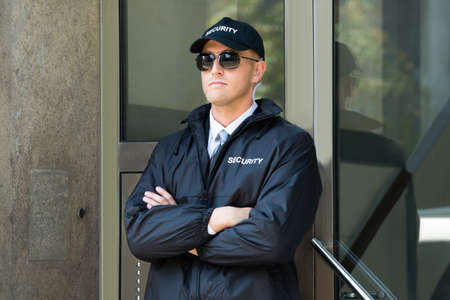 Jonge Mannelijke Beveiliging Standing At The Entrance Stockfoto