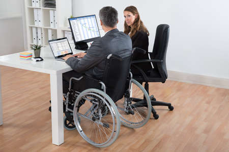 handicapped: Mature Disabled Businessman And Businesswoman Working Together On Computer In Office