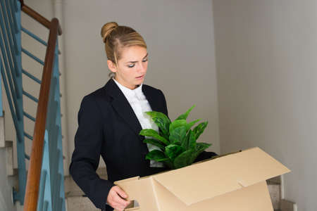 unemployed dismissed: Sad young businesswoman carrying her belongings in cardboard box at office Stock Photo