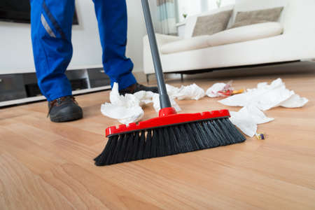 brooming: Low section of male janitor sweeping crumpled papers on floor in living room