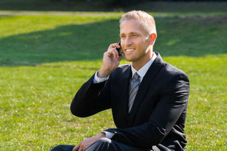 young businessman: Smiling Young Businessman Talking On Phone At Park Stock Photo