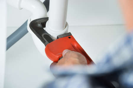 plumber tools: Cropped image of plumber fixing sink pipe with adjustable wrench in kitchen