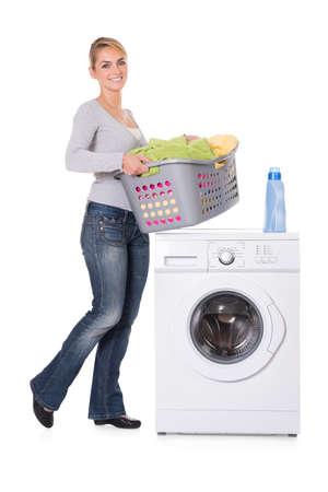 lavander: Mujer joven con el lavado y la ropa de pie junto a la lavadora sobre fondo blanco Foto de archivo