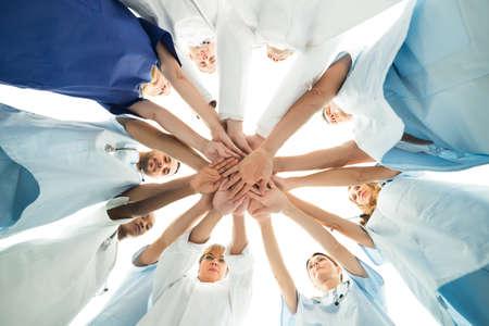 dentist: Directamente debajo de tiro del equipo médico multiétnica manos de apilamiento sobre el fondo blanco