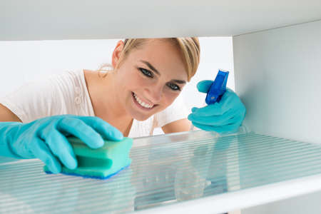 gospodarstwo domowe: Uśmiechnięta młoda kobieta czyszczenia lodówki z gąbką i sprayu w domu