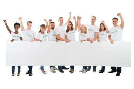 empty of people: Full length portrait of confident volunteers with arms raised holding blank billboard against white background