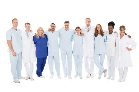 row: Full length portrait of confident medical team standing with arms around against white background Stock Photo