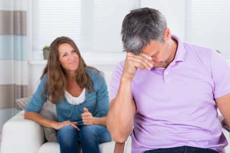 husband: Mature Woman Sitting On Sofa Shouting To The Depressed Man In Living Room