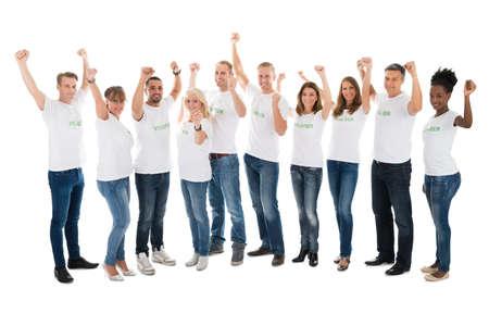 Full length portret van vertrouwen vrijwilligers met opgeheven armen staan in de rij tegen een witte achtergrond