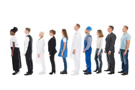 fila de personas: Completa vista lateral longitud de personas con diversas ocupaciones de pie en la cola contra el fondo blanco Foto de archivo