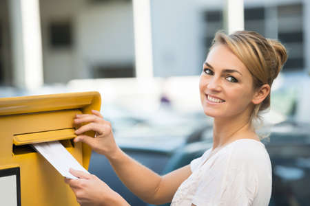 inserting: Happy young woman inserting letter in mailbox