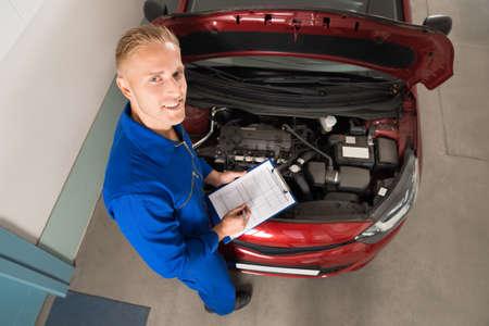 mecanico: Vista elevada de un mecánico coloca cerca del coche escrito en el portapapeles En el garaje Foto de archivo