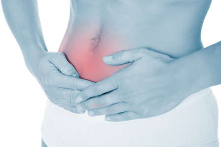 incontinence: Midsection of young woman suffering from stomach pain over white background