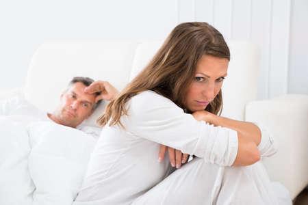 pareja en la cama: Mujer trastornada que se sienta en la cama con el hombre en el fondo