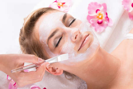 skin care products: Cropped image of beautician applying mask on customers face at salon Stock Photo