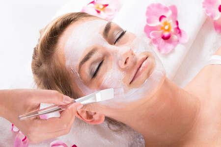 productos quimicos: Imagen recortada de esteticista aplica la máscara en la cara de los clientes en el salón