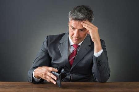 Geschokte zakenman met lege portemonnee aan bureau tegen grijze achtergrond zitten