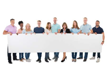 Pleine longueur portrait de confiance équipe commerciale créative tenant panneau blanc sur fond blanc Banque d'images