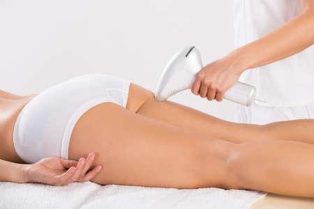 legs: Sección media de esteticista femenina que usa la máquina de láser en la pierna del joven cliente en el salón Foto de archivo