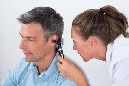 pacjent: Close-up z kobiet lekarz bada pacjenta z Ear Otoskop Zdjęcie Seryjne