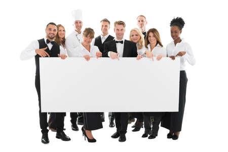 Portrait of confident restaurant staff holding blank billboard against white background 스톡 콘텐츠