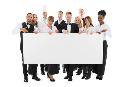Portrait of confident restaurant staff holding blank billboard against white background Foto de archivo