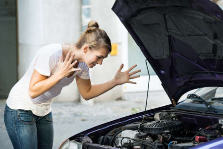 puzzlement: Frustrated young woman looking at broken down car engine on street Stock Photo