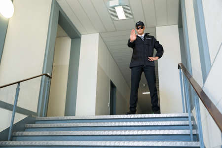 Confident Male Security Guard Standing In Front Of Entrance Making Stop Gesture
