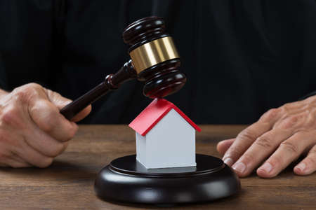 governments: Cropped image of judge holding gavel on house model at desk