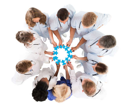 Directly above shot of medical team joining blue jigsaw pieces against white background Stock Photo