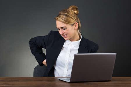 mujeres de espalda: Empresaria joven que sufre de backpain mientras que usando la computadora portátil en el escritorio sobre fondo gris