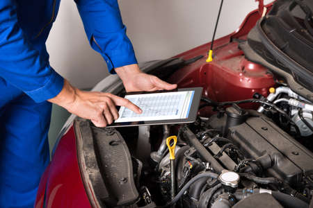 주차장에서 자동차 엔진을 검사하는 동안 디지털 태블릿을 사용하여 정비공의 근접