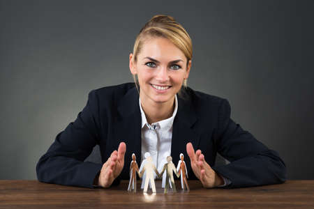 sheltering: Smiling young businesswoman sheltering paper team on desk over gray background