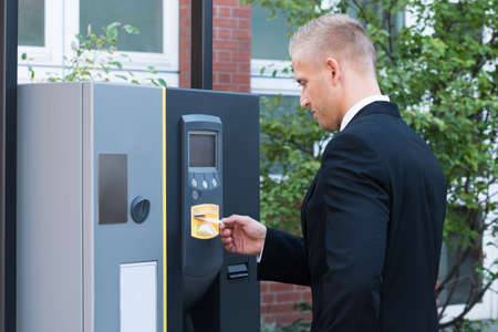 pay for: Young Man Standing And Inserting Ticket To Pay For Parking Stock Photo