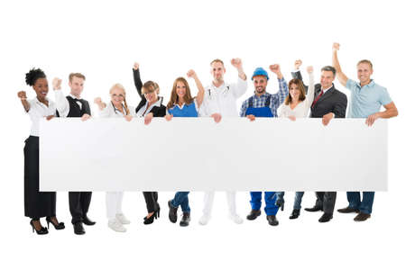 Group portrait of people with various occupations cheering while holding blank billboard against white background Stockfoto
