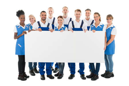 Cleaning team: Portrait of happy multiethnic janitors holding blank billboard against white background