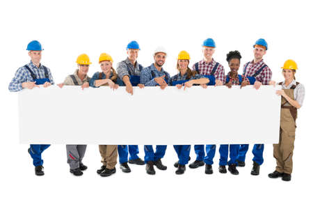 tradesmen: Portrait of happy construction workers holding blank billboard against white background