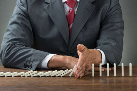 disaster: Midsection of businessman stopping dominoes falling on wooden desk