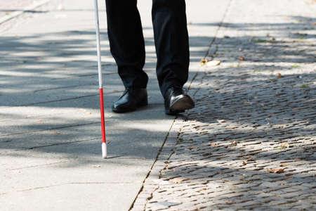 거리에 흰 막대기로 서있는 장님의 근접