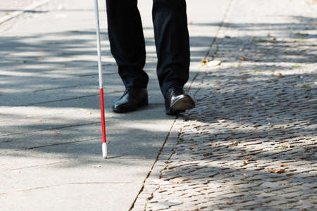 guy with walking stick: Close-up Of A Blind Man Standing With White Stick On Street