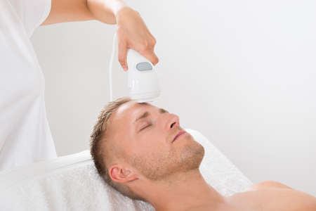 hair treatment: Young Man Receiving Laser Hair Removal Treatment At Beauty Center Stock Photo