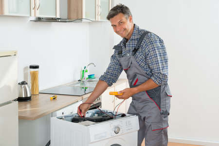 wash machine: Full length of technician checking washing machine with digital multimeter in kitchen