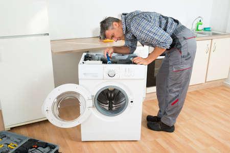 personas de pie: Longitud total de manitas de comprobar la lavadora con la linterna en la cocina