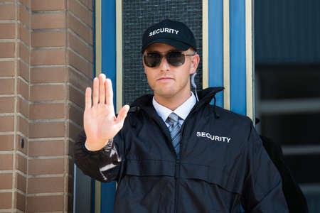 guardia de seguridad: Primer plano de un guardia de seguridad Hombre Haciendo muestra de la parada con las gafas de desgaste de la mano