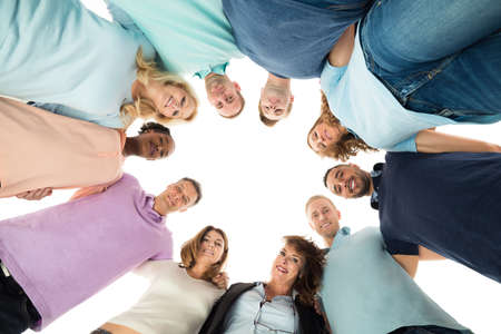 directly below: Directly below portrait of creative business people standing in huddle against white background
