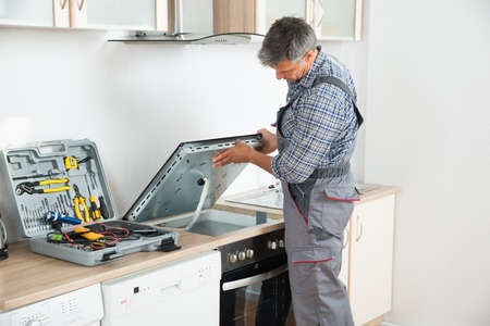 home appliance: Photo Of mature repairman examining stove in kitchen