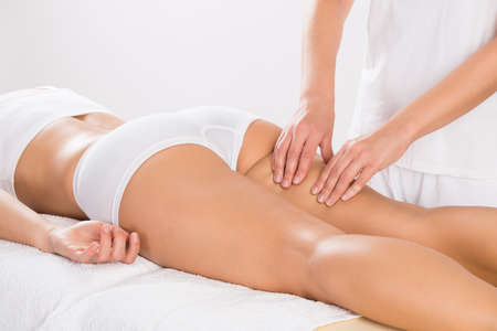 Midsection of female customer receiving leg massage in salon