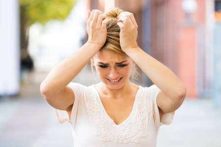 suffering: Sad young woman suffering from headache outdoors Stock Photo